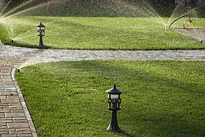 Lawn Sprinklers in Peoria IL watering the grass alongside a brick path