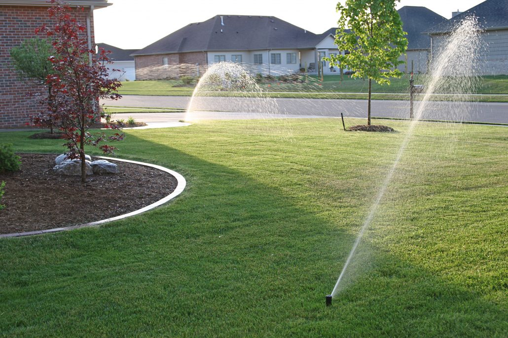 Front yard of home being watered by lawn sprinklers in Bloomington IL
